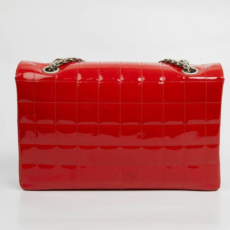 CHANEL 2.55 bag in red patent leather. The attributes are matt silver metal. The inside of the flap is in red leather while the storage space is in the same color fabric with a large zipped pocket. It can be worn on the shoulder or crossed. Apart