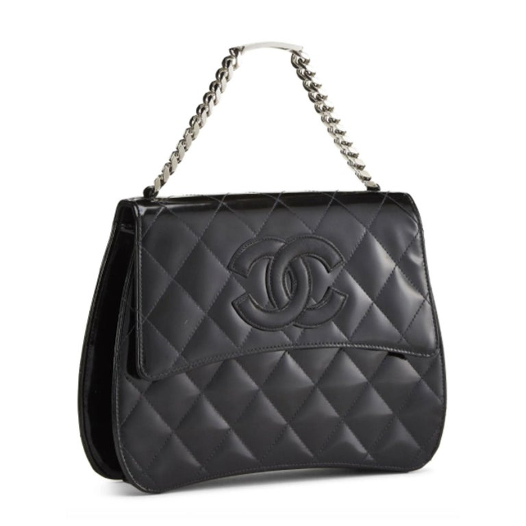 Vintage mid 90s Chanel handbag crafted in black quilted patent leather, featuring interlocking 'CC' applique on front flap and finished with silver-tone metal ID Bracelet top handle. Chain-link Top Handle Magnetic Snap Closure On Flap Interior Zip