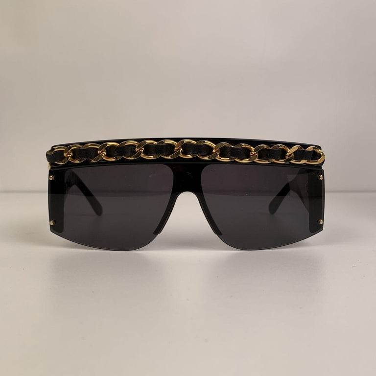 Super Rare 1990s Chanel Shield Sunglasses. This model was worn by Lady Gaga. Mask shaped, with gold metal & black interwoven leather classic CHANEL chain starting from the arms, all the way through the front. Model refs: 01455 - 94305. Made in
