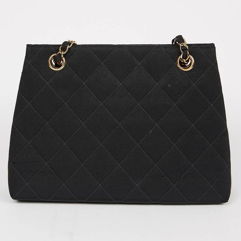 Vintage is in the spotlight today with this lovely bag from Maison Chanel in black cotton. The hardware is in metal and vintage gold. Closure by press button.  The lining is in shiny black satin with a large zipped pocket. It has its hologram and