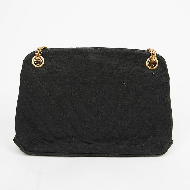 This beautiful little vintage evening bag is in black jersey. The jewelry is in golden metal, its chain can be worn in single or double. The bag has two storage bellows with a zipped pocket on each side separated by a pocket with a wallet clasp.