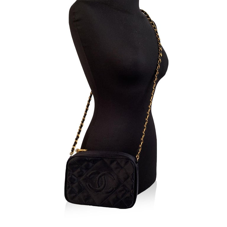 Vintage Chanel crossbody Camera Bag crafted in black quilted satin with CC logo on the front. It features gold metal hardware, single iconic shoulder strap with interwoven satin, upper zipper closure and leather lining. 1 side zip pocket inside.