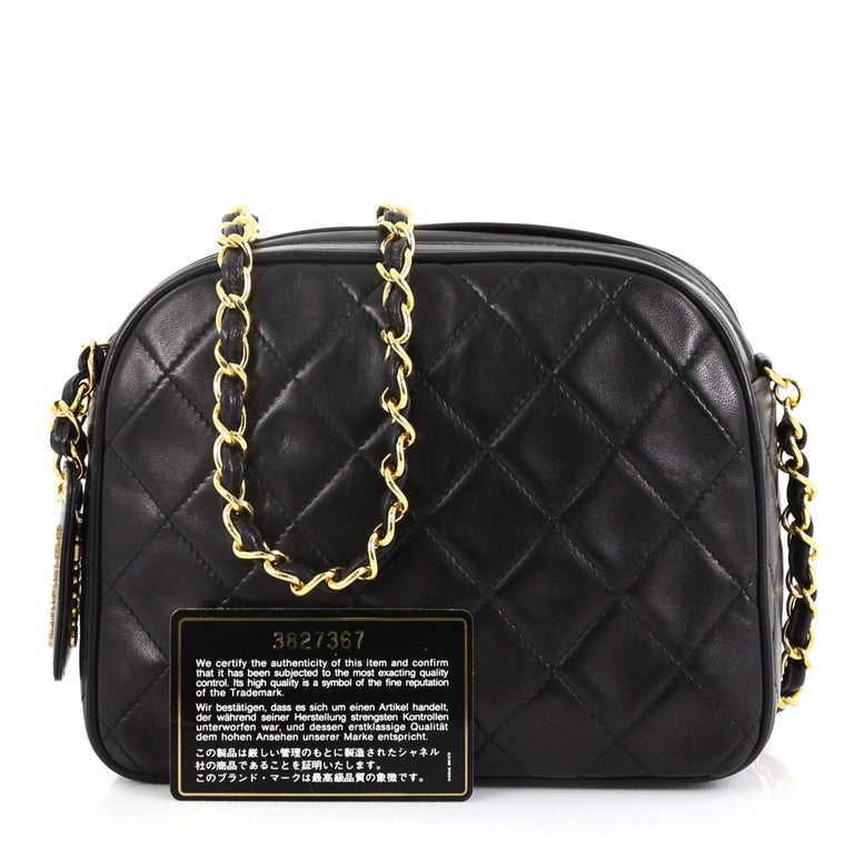 This Chanel Vintage Chain Camera Bag Quilted Lambskin Small, crafted in black quilted lambskin leather, features woven-in leather chain strap and gold-tone hardware. Its top zip closure opens to a black leather interior with zip pocket. Hologram