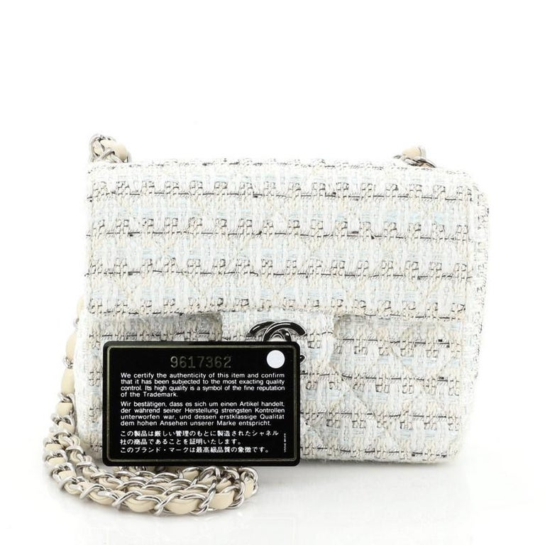 This Chanel Vintage Chain Handle Flap Bag Quilted Tweed Mini, crafted from white multicolor quilted tweed, features woven-in leather chain link straps and silver-tone hardware. Its CC turn-lock closure opens to a neutral leather interior with zip
