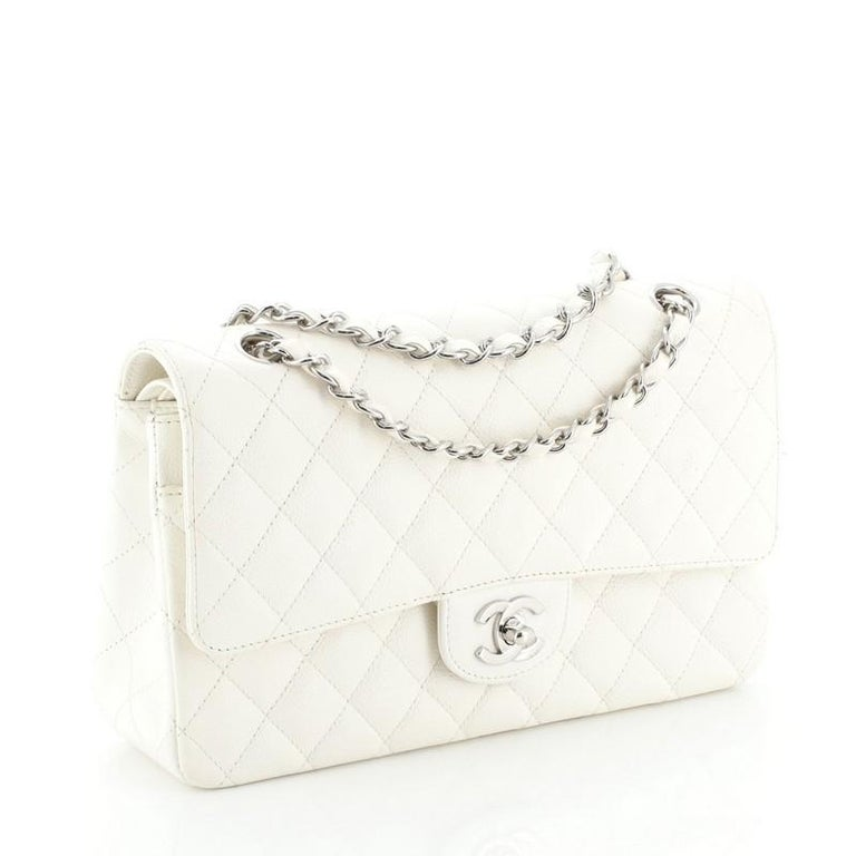 This Chanel Vintage Classic Double Flap Bag Quilted Caviar Medium, crafted from white quilted caviar leather, features woven-in leather chain strap, exterior back pocket and silver-tone hardware. Its double flap and frontal CC turn-lock closure