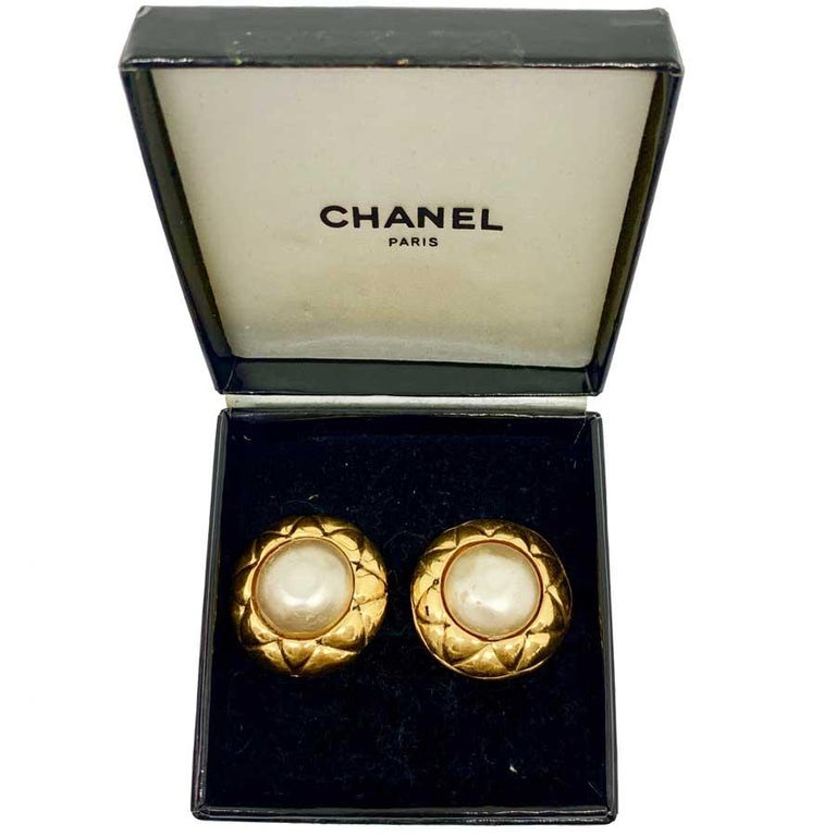 Iconic pair of CHANEL earrings from the 80s. Vintage clip in gold metal with a quilted effect and a pearly fantasy pearl in its center. The clips hold well to the ears. Made in France. The clips are in good condition. The metal is in very good