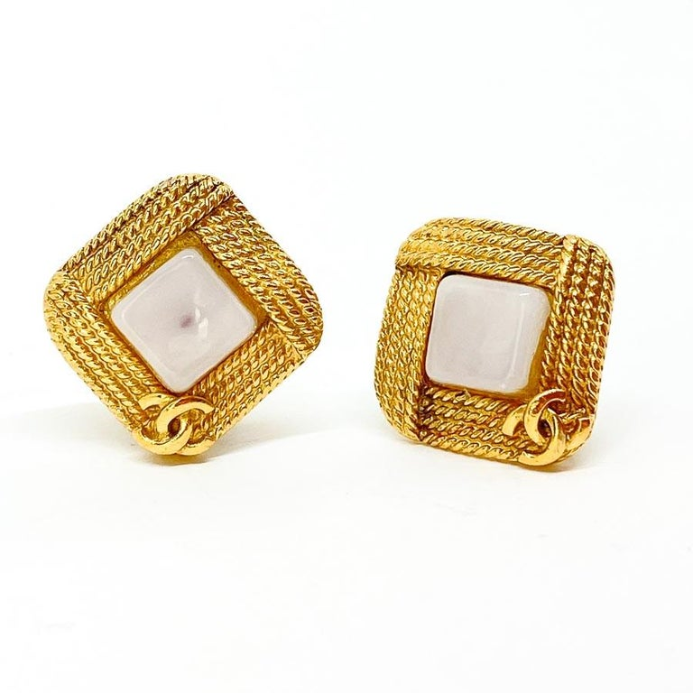 The earrings are clips signed by Maison CHANEL. They are square in shape of metal gilded with fine gold and have cabochons of white glass paste in the center. They are also adorned with the brand's initials CC. Put vintage chic in your jewelry