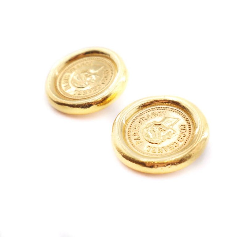 The earrings are from Maison CHANEL. They come in the form of golden coins with the Coco CHANEL effigy in its center encircled by the words: COCO CHANEL PARIS FRANCE. Characteristics of the Coco CHANEL golden clips The clips are in perfect condition