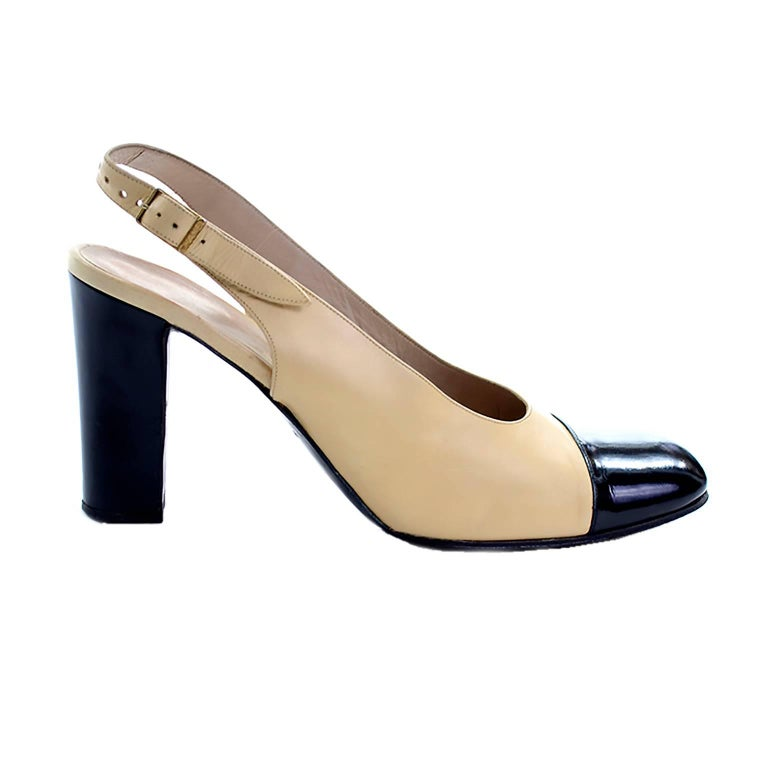 These classic two tone slingback Chanel pumps have a soft leather upper in a cream shade, with shiny black patent leather cap toe and block heel. The strap secures with a buckle at the ankle.  Made in France and labeled a European size 39.5 which is