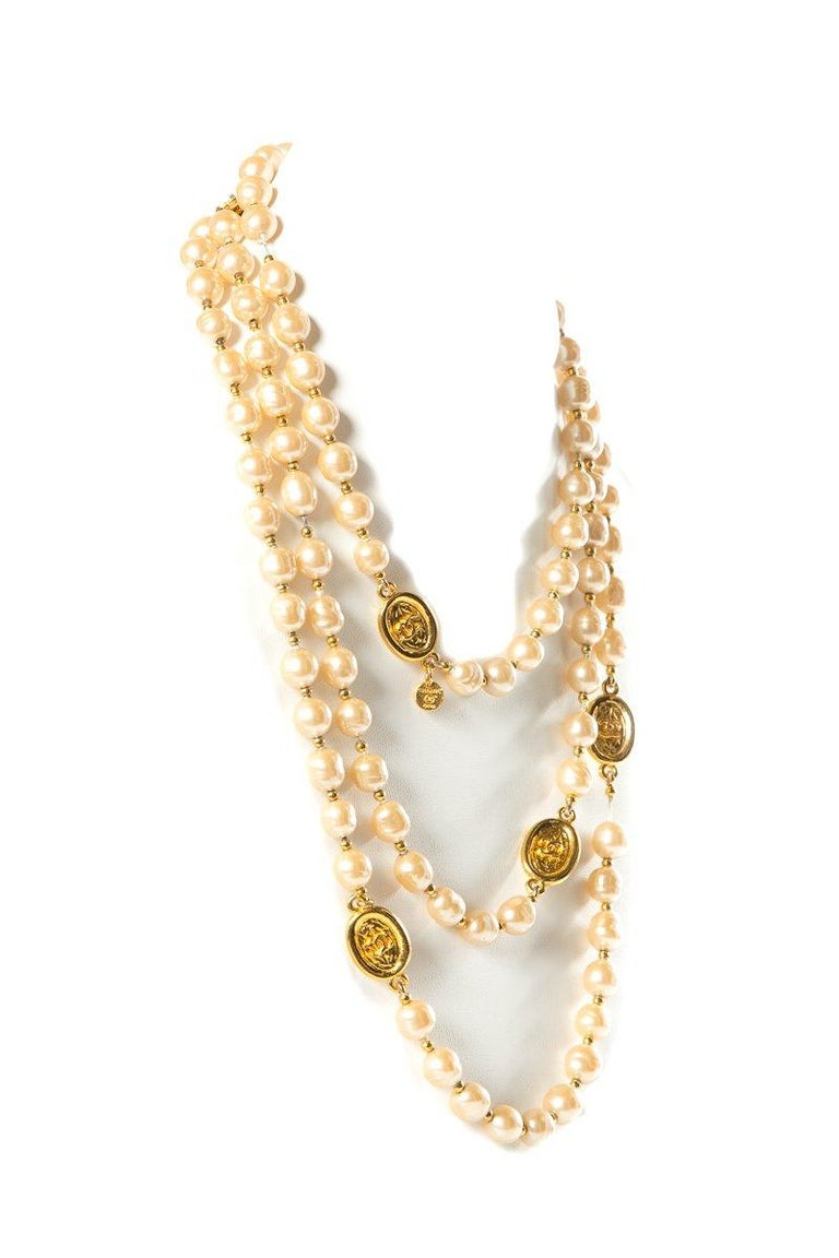 Chanel vintage faux pearl Sautoir necklace with gold-tone interlocking CC disk stations and gold-tone beads. This necklace is dated 1981 and measures 64