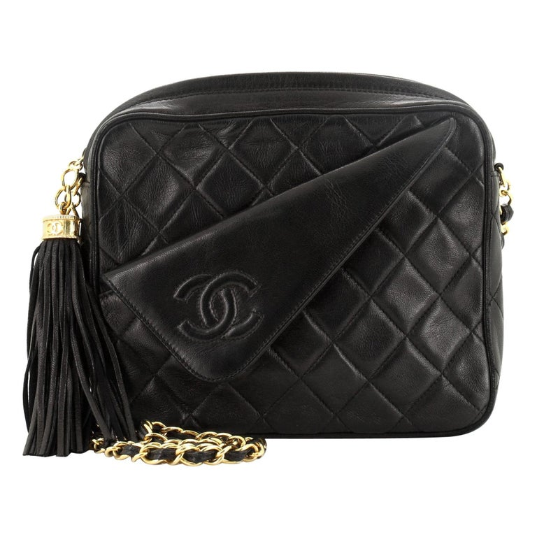 This Chanel Vintage Front Pocket Camera Bag Quilted Lambskin Small, crafted in black quilted leather, features a chain link strap, front flap pocket with CC stitched logo, and gold-tone hardware. Its top zip CC charm tassel closure opens to a black