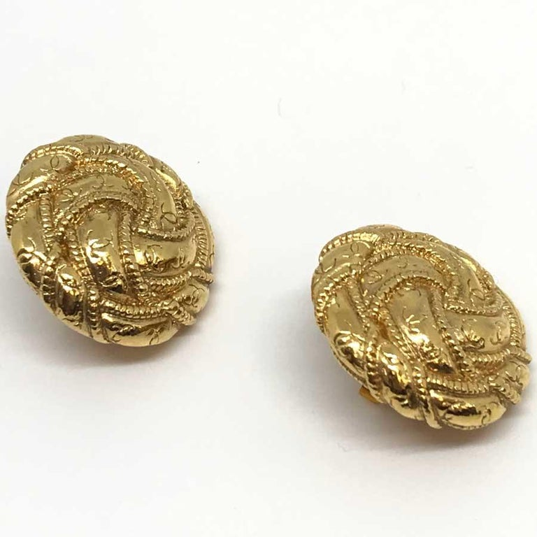 Lovely clips covered with twists on which are engraved a multitude of CC (Chanel emblem).  Made In France. Gilt metal. 3cm diameter. Very good condition. Will be delivered in a black box (not Chanel) embellished with a Chanel ribbon and camellia.