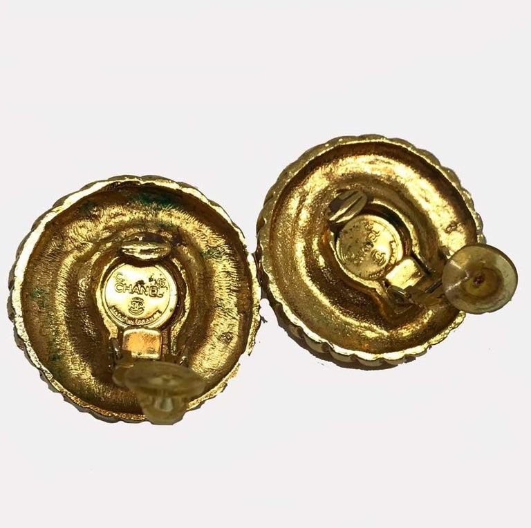 Two spheres of twisted metal, gold in color with mother-of-pearl glass paste in each of their centers. CHANEL clips are vintage and in very good condition. Made of twisted golden metal with its pearl in pearly glass paste, it measures 3 cm in