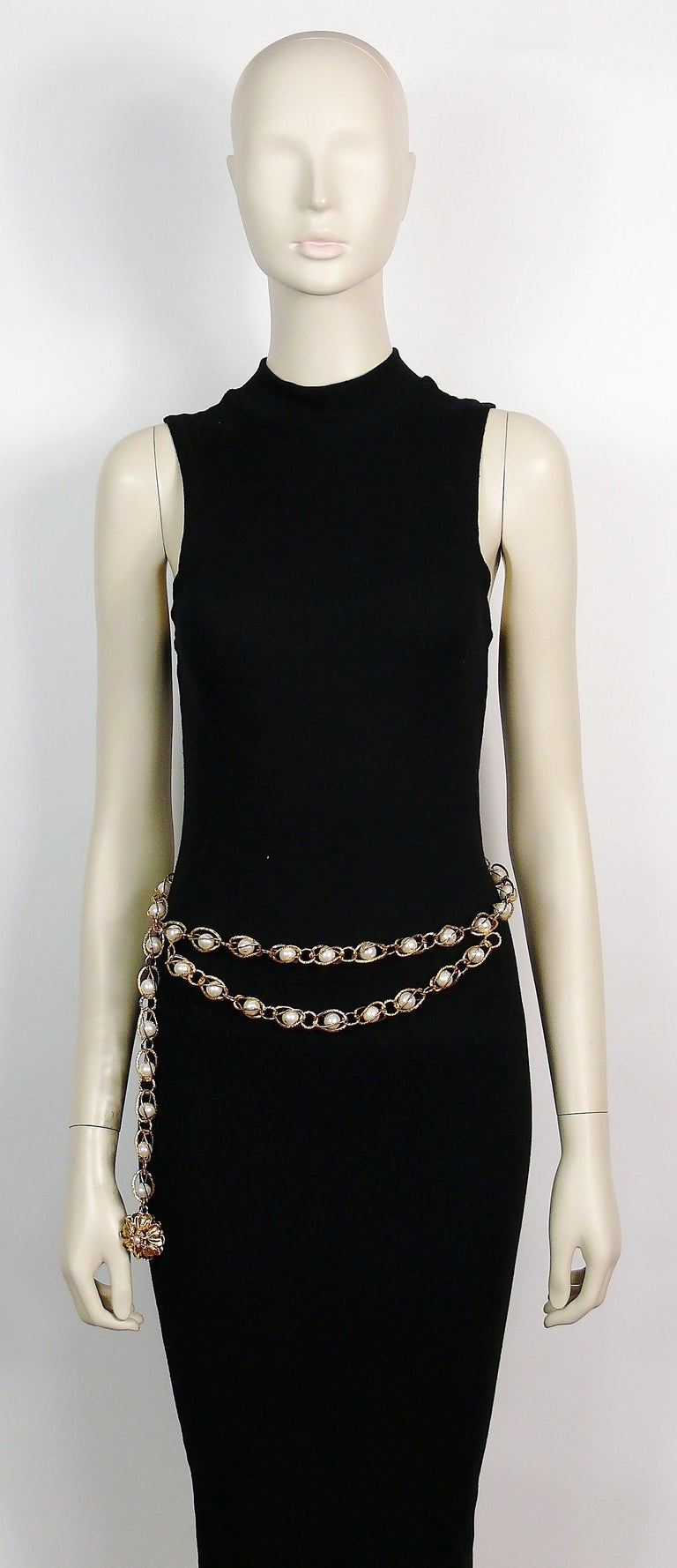 CHANEL gold toned belt featuring a chain-link of gold spheric cages encasing faux pearls, two hanging tiers and gold flower charm.  Hook clasp. Adjustable length. One size fits all.  Embossed CHANEL.  Indicative measurements : max. wearable length