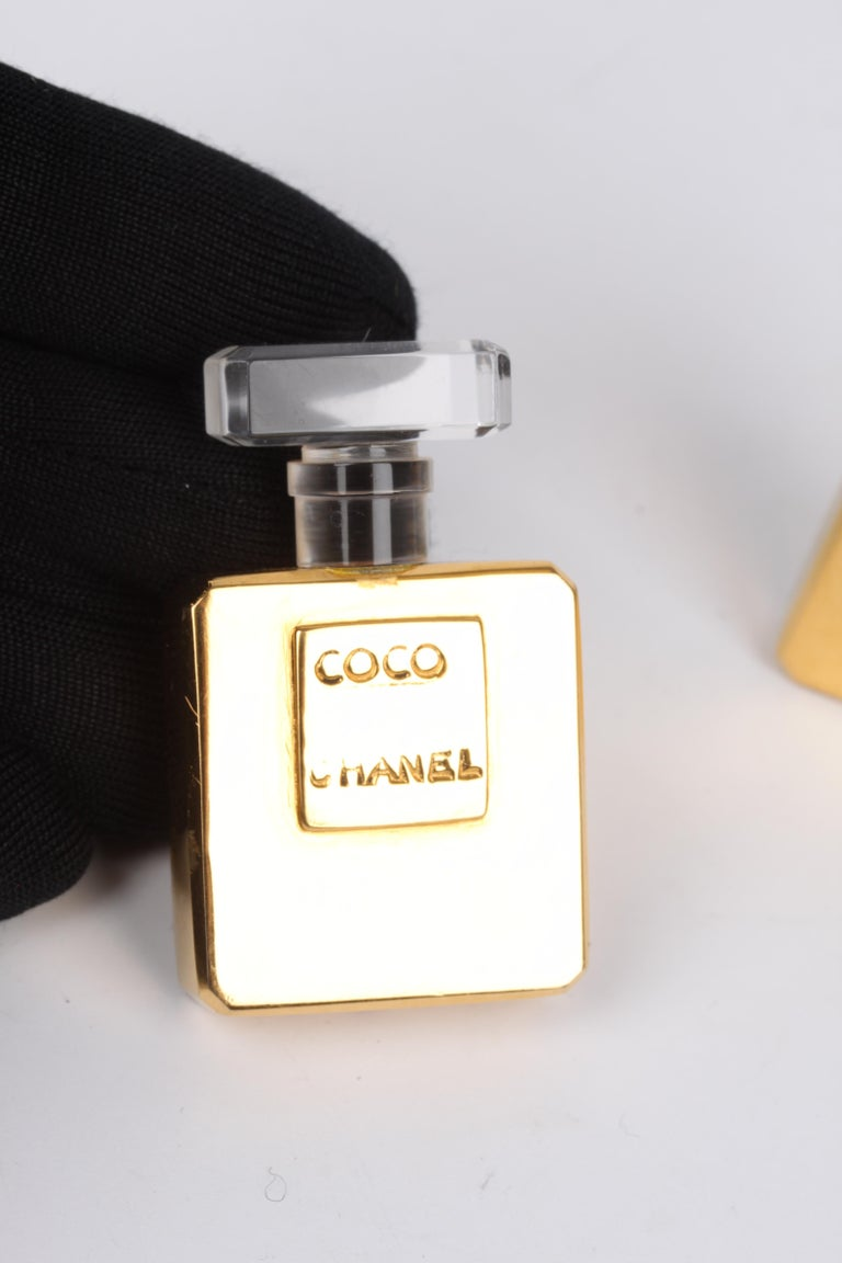 This wonderful set of Chanel earrings is from the 80's, true vintage!  Clip-on earrings in the shape of a gold-tone perfume bottle, of course with the words COCO CHANEL embossed. On top the bottle is translucent. Statement pieces!  In good vintage