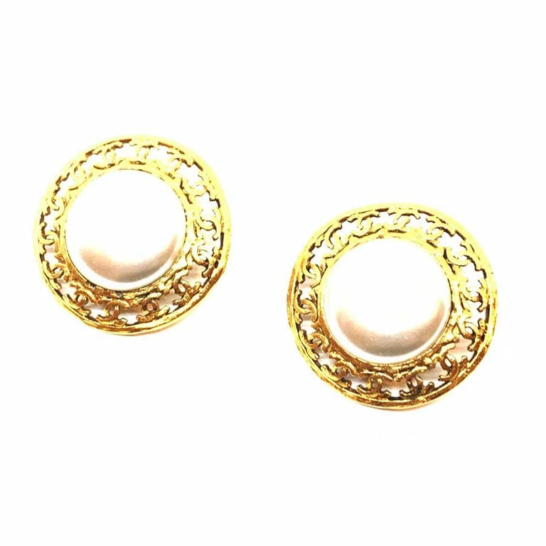 The pair of earrings is a vintage model from Maison CHANEL. Round in shape, they each have in their center a pearly ball encircled by a frieze of CC in metal gilded with fine gold. All the vintage spirit of CHANEL in this pair of clips to keep as a