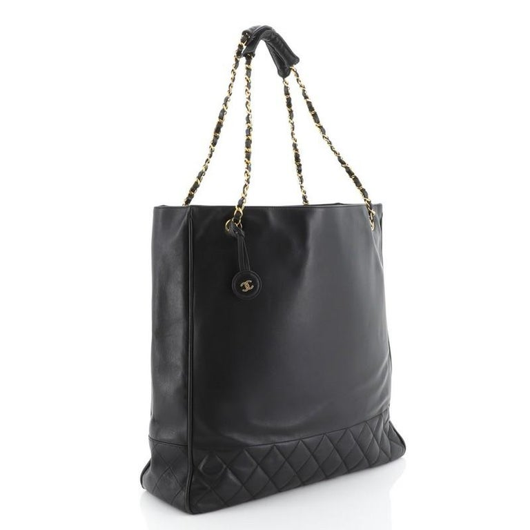 This Chanel Vintage Shopping Tote Lambskin Large, crafted from black lambskin leather, features woven-in leather chain straps and gold-tone hardware. It opens to a black leather interior. Hologram sticker reads: 1133521.   Estimated Retail Price: