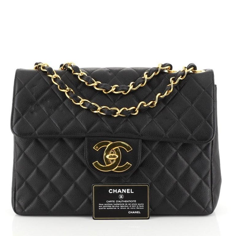 This Chanel Vintage Square Classic Single Flap Bag Quilted Caviar Jumbo, crafted from black quilted caviar leather, features woven-in leather chain strap, exterior back slip pocket, and gold-tone hardware. Its CC turn-lock closure opens to a black