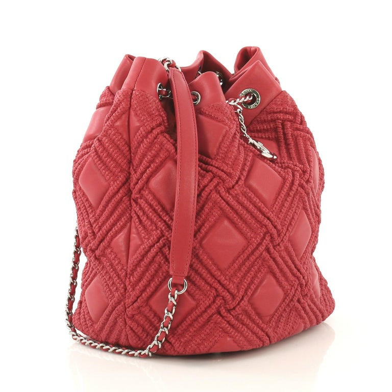 This Chanel Walk of Fame Drawstring Bucket Bag Stitched Lambskin Small, crafted from red stitched lambskin leather, features woven-in leather chain strap with leather pad, CC logo charm, and silver-tone hardware. Its chain strap that doubles as a