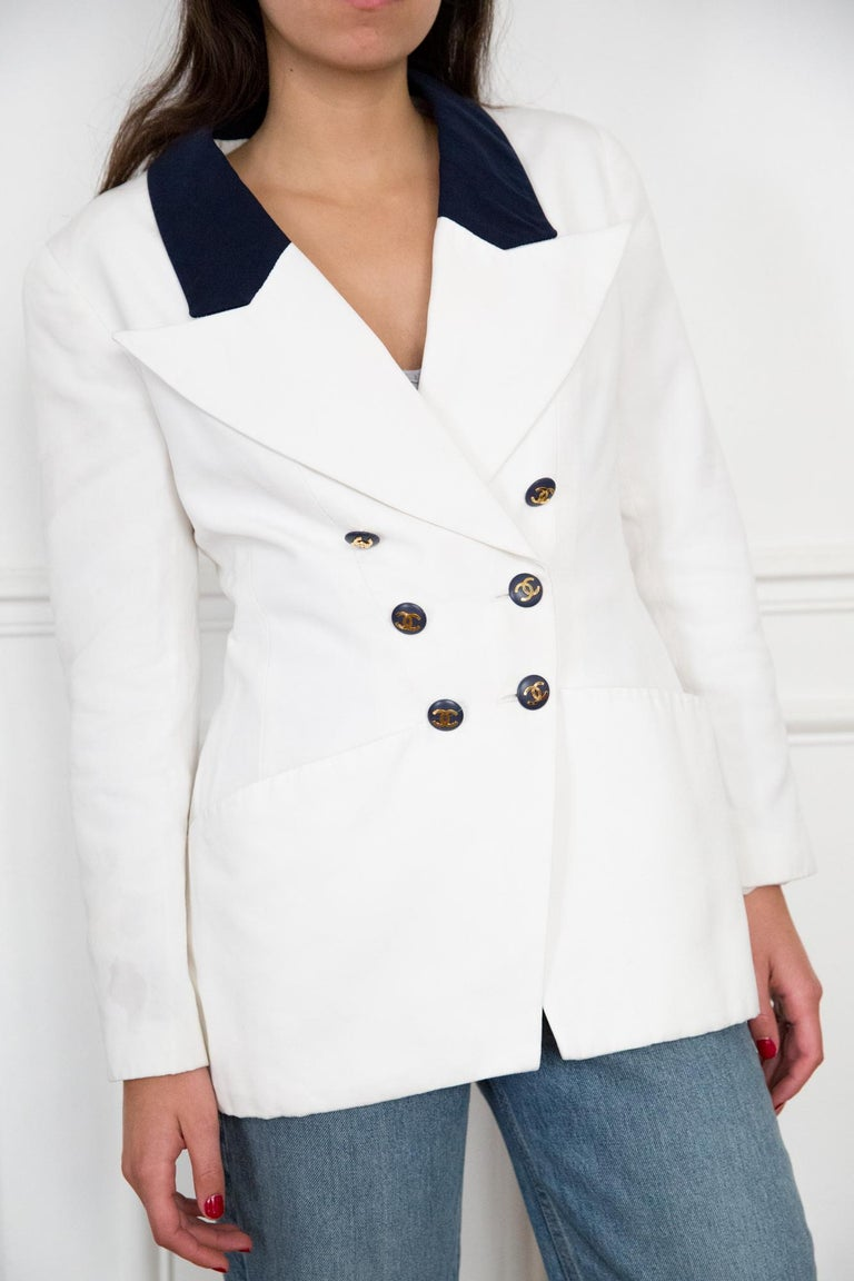 Chanel white long cotton Chanel blazer featuring a long length, navy contrasted details, front logo buttons, long sleeves with logo buttons, and a silk logo lining. Composition: 100%cotton Lining:100%silk In excellent vintage condition. Made in