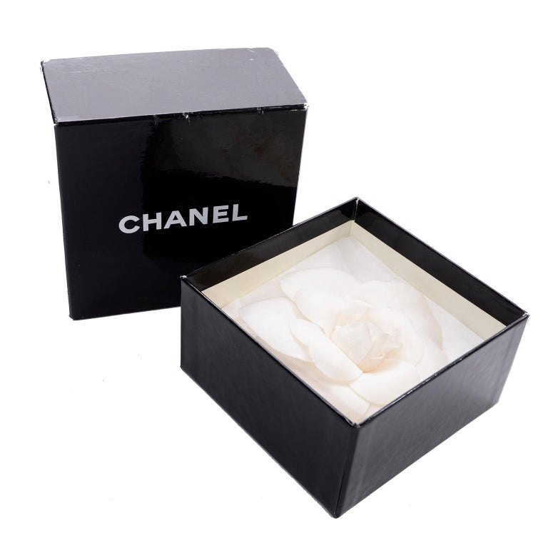 This is a collectible white Chanel Camellia Flower Pin with the Chanel gold tone plate: