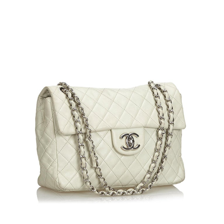 The Classic Jumbo Flap features a caviar leather body, a chain shoulder strap, a front flap with interlocking Cs in gold-tone hardware and a twist lock closure, an exterior back slip pocket, and an interior zip and slip pockets. It carries as B