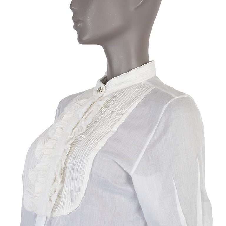 Chanel 3/4-sleeves shirt in white light cotton (assumed as tag is missing). With pleated band collar, pleated bib, fan ruffles on the front. one-button square cuffs, and side slits. Closes with one rhinestones and pearls button and concealed buttons