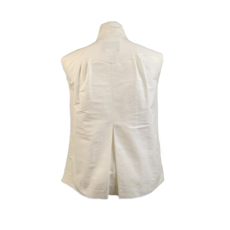 Chanel white grosgrain vest/sleeveless top. The vest features sleeveless styling, a button closure on the front, bow detail on the neckline and pleating detailing. 2 flap pockets on the chest. Unlined. Composition: 62 % Cotton, 26% Nylon, 9 %