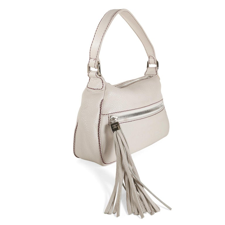 Chanel White Leather Tassel Shoulder Bag- excellent condition A secure zippered top and fashionable oversized tassel make this Chanel just right for every day.   White pebbled leather is accented with dark red contrast stitching and silver hardware.
