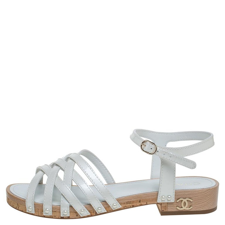 Combining comfort, class, and style, these flat sandals from Chanel are one of a kind! They have been crafted from white patent leather in an open-toe silhouette and styled with criss-cross straps on the vamps. They feature ankle straps with buckle