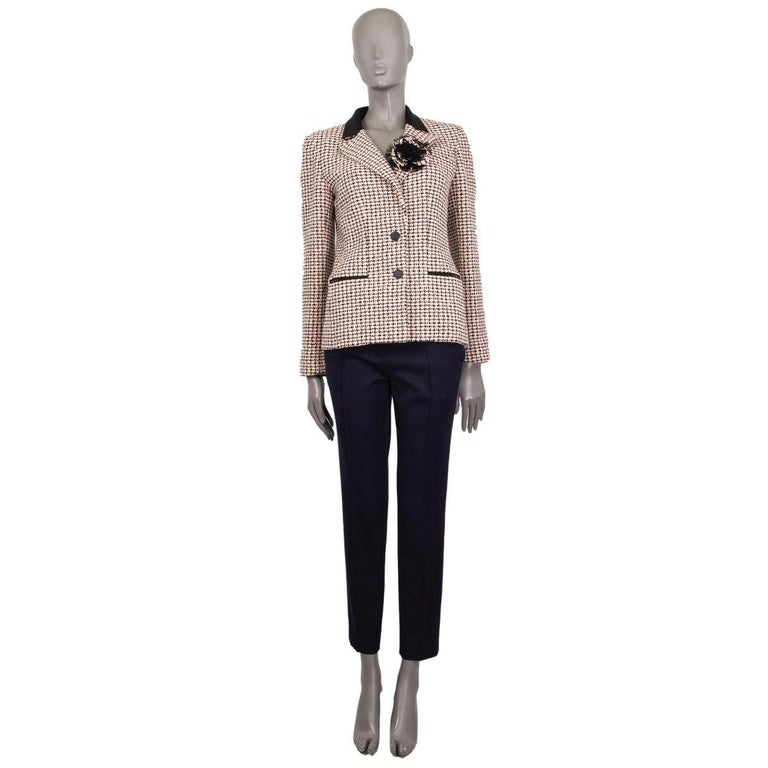 Chanel houndstooth tweed blazer in black, off-white and rose cotton (100%) with a notch collar, flower-brooch and two slit pockets. Closes on the front with buttons. Cuffs fasten with buttons. Lined in silk (100%). Has been worn an is in excellent