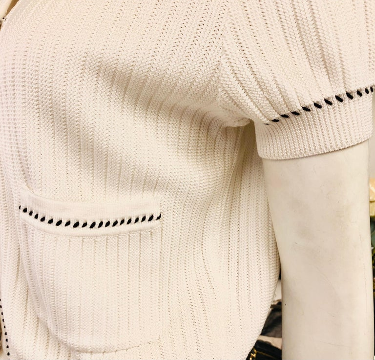"""- Chanel white short sleeves knitted cotton cardigan from spring 1996 collection.   - Black and white """"CC"""" button closure.   - Two front pockets.   - Size 44.  - 100% cotton."""