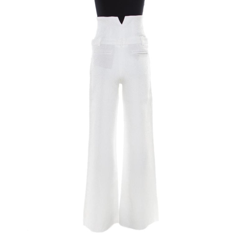 Chanel's elegant white trousers are designed with wide legs. They are crafted with a cotton blend and have a textured finish. The easing silhouette of these trousers makes them a comfortable piece of clothing which, when paired with a fitted blouse,