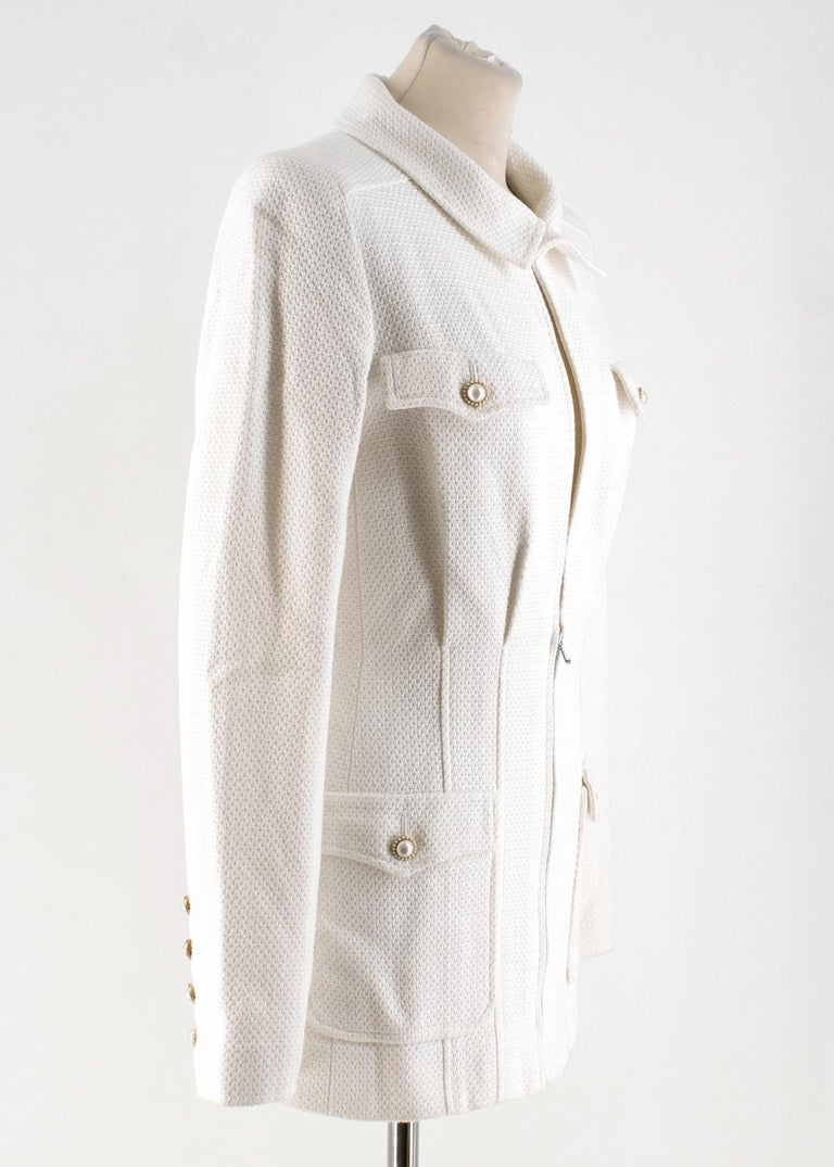 Chanel White Tweed Jacket  - White, mid-weight tweed jacket - Padded shoulders, long sleeves  - Breast pockets - Front flapped pockets - Faux-pearl embellished buttons - Round neck, hook-and-eye fastening - Gold-tone metal hardware, logo embroidery