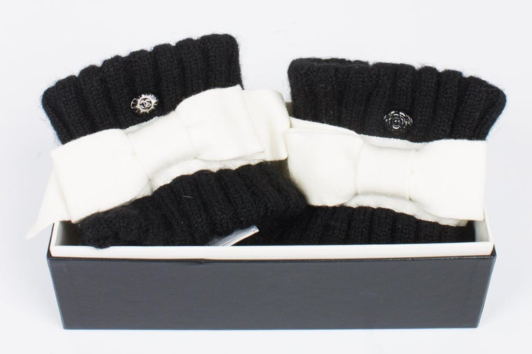Are these wrist warmers or cuffs? Eighter way, they are great!  These wide black cuffs are meant to wear on the wrist have a large white bow. A black camellia button on one, a black/silver button with interlocking CC on the other. Limited