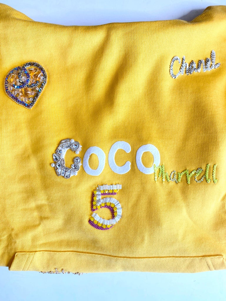 Step up your streetwear game with this rare Chanel X Pharrell hoodie! Circa 2019, this sunflower yellow ultra soft hoodie is decorated with glittery Chanel appliqués scattered throughout including rhinestone hearts, the number 5, and the