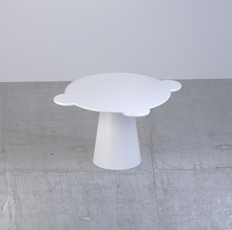 Donald is a multifunctional table with a sculpturally cosmic aspect and colorful circular shapes.  The sculptural silhouette has a wooden structure composed of a truncated cone that supports a round top adorned with three semi-circular flaps,