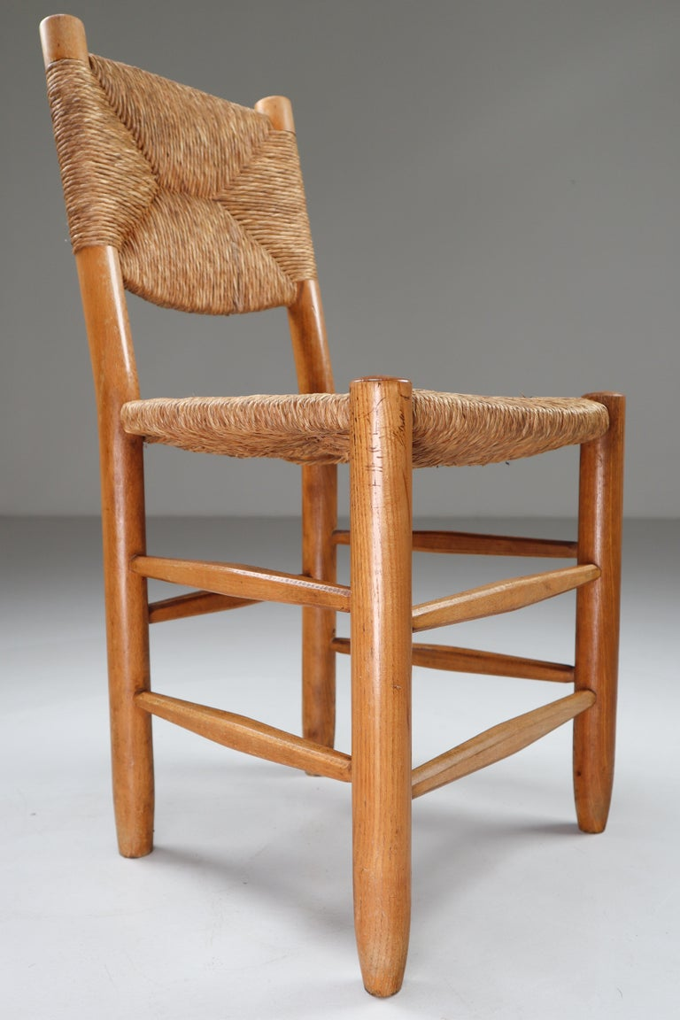 Characteristic chair of wood and straw in one of the quintessential midcentury designs of their creator, the famous French furniture maker Charlotte Perriand. The chair is in a great original condition and have a great patina and natural wear to the