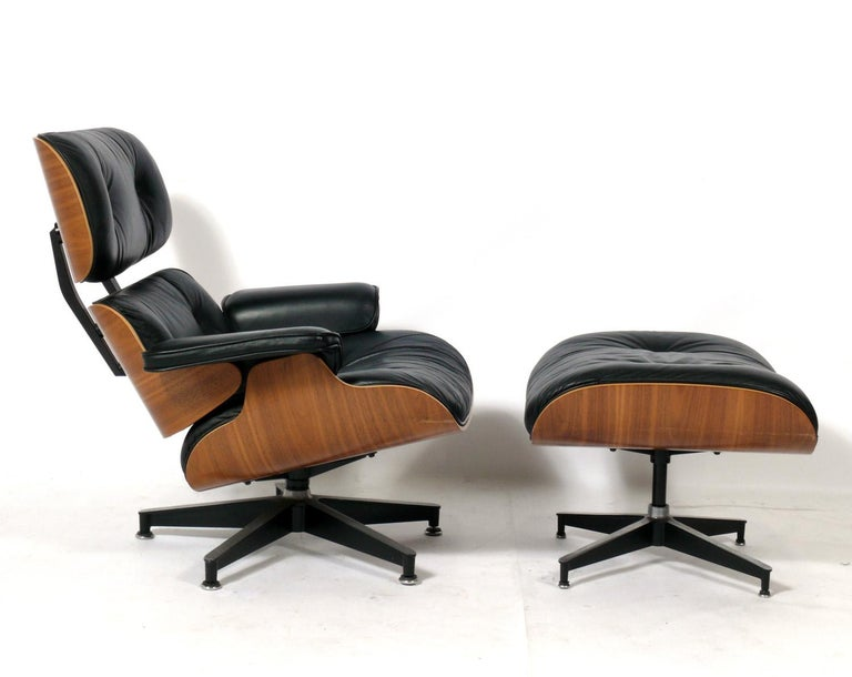 Iconic walnut and black leather lounge chair and ottoman, Model 670 and 671, designed by Charles and Ray Eames for Herman Miller, American, circa 1990s. Signed with Herman Miller tag underneath. Perfectly broken in like your favorite baseball glove.