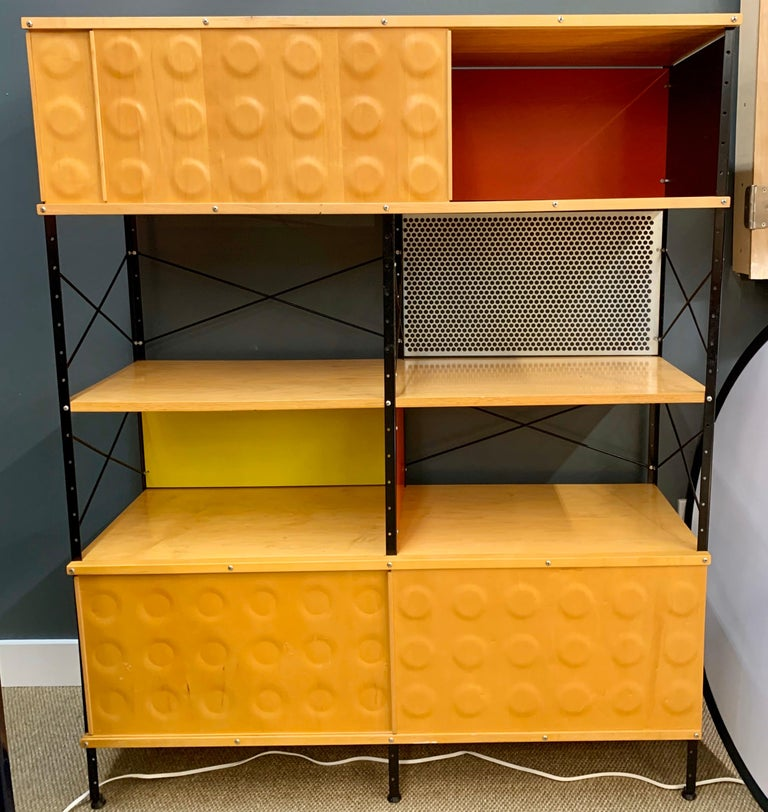 The Charles & Ray Eames ESU 400 N storage unit for Herman Miller. In the USA. The design features plated steel uprights, and crossed metal struts inspired by industrial warehouse shelving. The walnut wood finish has a beautiful grain with a