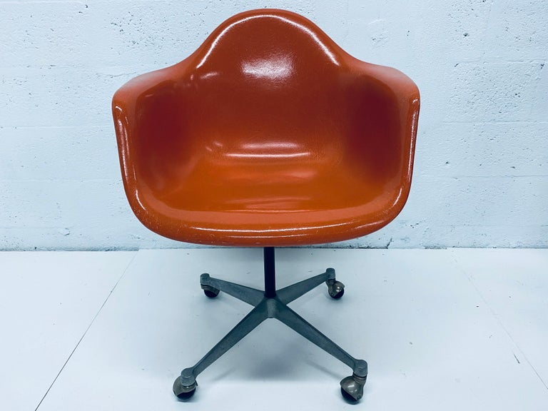 Original Charles and Ray Eames designed burnt orange moulded fiberglass desk chair on casters for Herman Miller, 1960s. Chair swivels smoothly. Not height adjustable.