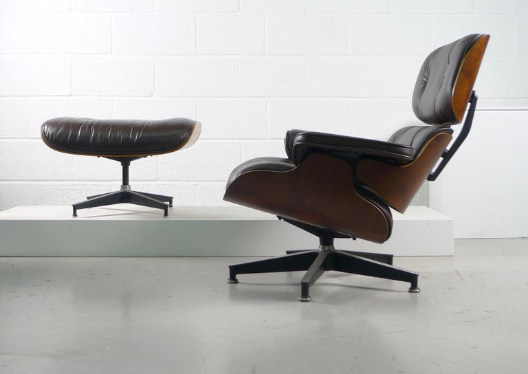 Charles and Ray Eames model 670/671 lounge chair and ottoman for Herman Miller USA, 1956.   Rosewood shells and dark chocolate brown leather, this example from the 1970s. Multiple labels to both chair and stool.   Possible free delivery to