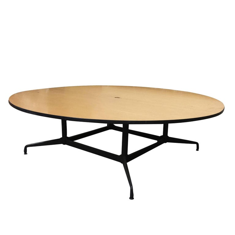 Large 8' foot Charles and Ray Eames designed round conference table by Herman Miller.   The table features a large two-piece round laminate oak veneer wood top with a steel and aluminum base. This is a conference table that will easily impress,