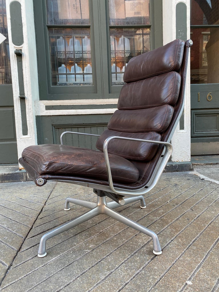 Eames soft pad lounge chair in brown leather for Herman Miller. Chair is about 25 years old and shows wear as seen in the photos. Seat area has some roughness to the leather. Wear marks to edges or corners. I had new foam put in the seat cushion.