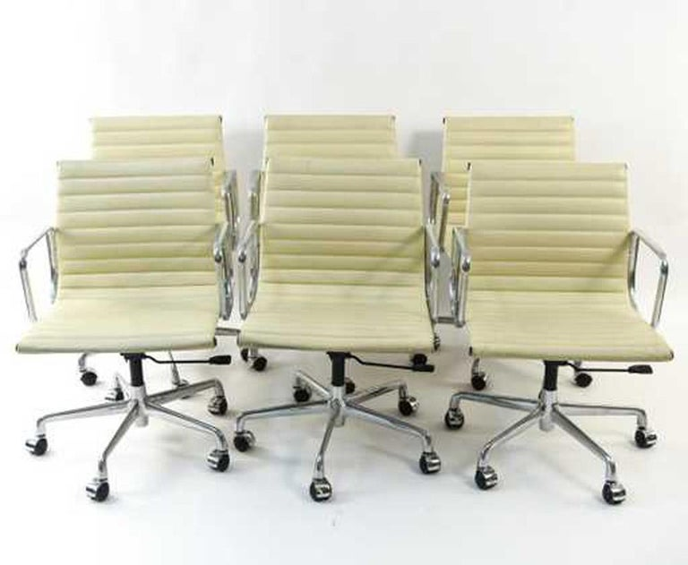 Eames aluminum management office armchairs for Herman Miller. Condition: Small/tear scratches to leather, fading and discoloration to chrome. Eames EA335 management office chair in white leather with five-star base, spindle and tilt-swivel