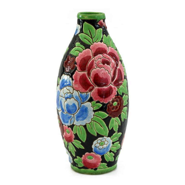 Stunning Belgian Art Deco Boch Freres Keramis art pottery vase decorated with red and blue peonies designed by Charles Catteau. The lightly potted vase of tall bulbous shape is finely incised and hand painted in bold colors with large peony blooms