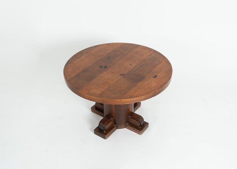 A quadrupedal pedestal coffee table in oak by Charles Dudouyt possesses a round, and a thick columnar support.