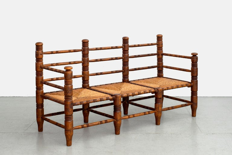 Charles Dudouyt bench with 3 woven seats and signature carved legs and back.  Newly rushed seats with wonderful patina to oakwood.
