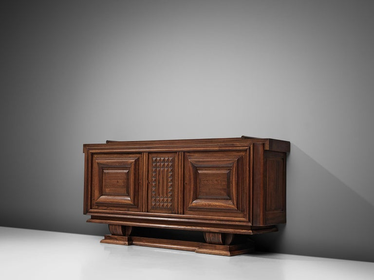 Charles Dudouyt, sideboard, darkened oak, France, 1940.  Sturdy credenza in oak that is truly a sculptural piece. This three-door sideboard is equipped with several shelves that provide plenty of storage space. The graphic, rhythmical door panel of