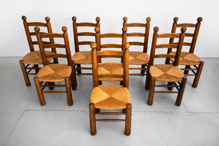 Set of 8 French dining chairs by Charles Dudouyt. Beautiful natural oak frames with woven seats. Solid and sturdy.